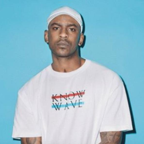 Skepta in front of a blue background